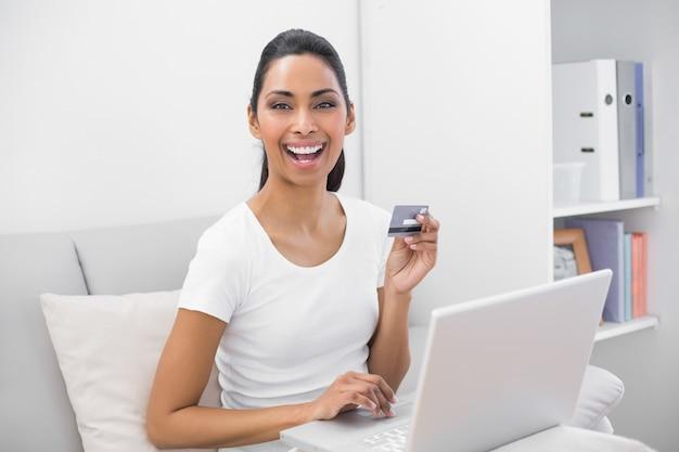 Compras de casa de mulher de cabelos escuros feliz com seu notebook
