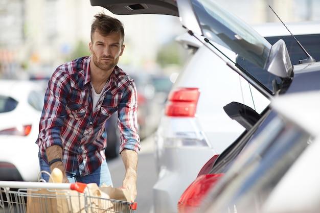 Compras de homem embalagem no carro