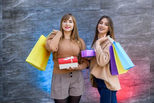 Compras de natal. duas mulheres felizes com sacolinhas coloridas posando depois das compras