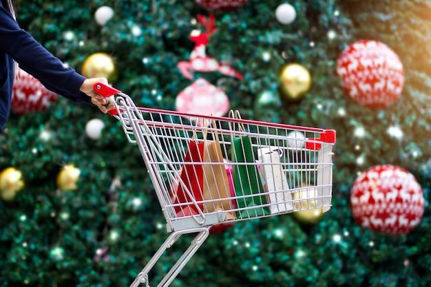 Compras de natal - mulher compras com sacos no carrinho de compras no ornamento e natal tr