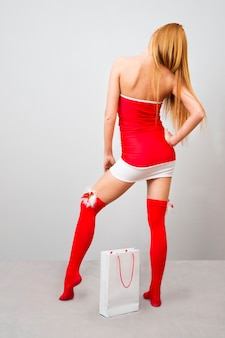 Compras de natal. mulher linda em um vestido vermelho no natal em um fundo cinza.