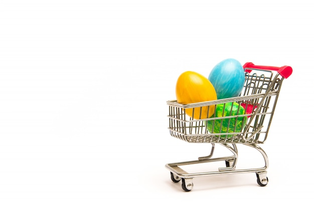 Compras de páscoa. ovos coloridos feitos à mão no carrinho. negócios e venda na primavera