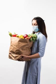 Compras de supermercado em pandemia - linda jovem indiana usando máscara protetora enquanto segura um saco de papel com vegetais e frutas durante a epidemia de vírus