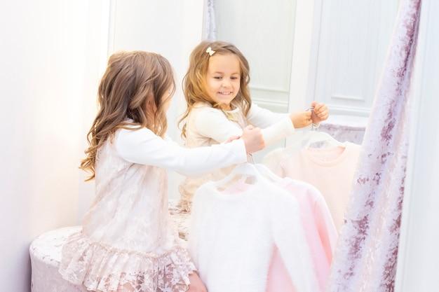 Compras. descontos. menina viciada em compras. garota experimentando um lindo vestido rosa suavemente no provador da boutique. centro comercial, compras. emoções