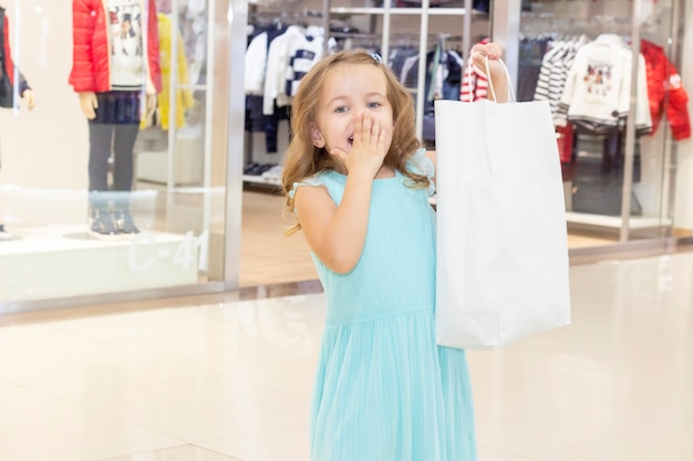 Compras. descontos. menina viciada em compras. menina com sacolas de compras nas mãos. sacos brancos copyspace. centro comercial, compras. emoções