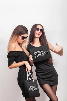 Compras. duas mulheres segurando sacolas pretas em vendas de sexta-feira negra