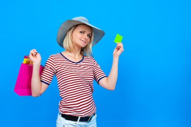 Compras e vendas de verão. mulher caucasiana loira com chapéu de verão segurando sacolas roxas e mostrando o cartão de crédito verde
