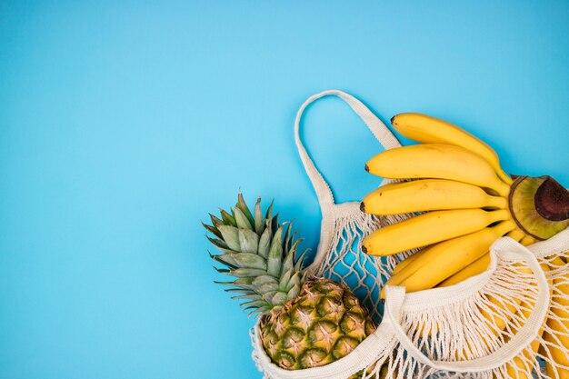 Compras eco amigável saco com frutas orgânicas de banana e abacaxi sobre fundo azul