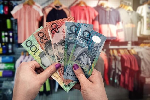 Compras em loja de roupas, dinheiro em mãos femininas