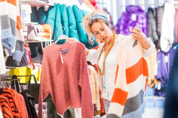 Compras em loja de roupas para uma mulher caucasiana bonita escolhendo um suéter