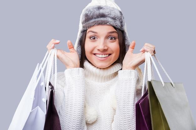 Compras em qualquer clima. mulheres jovens felizes usando roupas quentes de inverno e segurando pacotes com compras em pé contra um fundo cinza