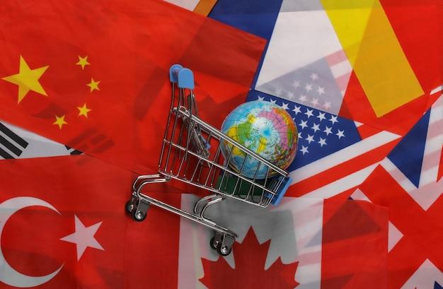 Compras internacionais. carrinho de supermercado com o globo no fundo de muitas bandeiras dos países