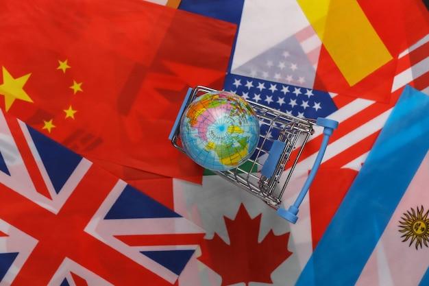 Compras internacionais e globais. carrinho de supermercado com o globo no fundo de muitas bandeiras dos países