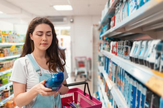Compras. jovem mulher bonita lendo um rótulo de xampu na loja
