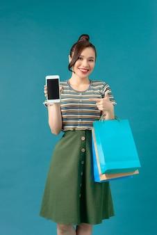 Compras. jovem mulher sorridente segurando a bolsa e o celular maquiar o polegar no feriado negro de sexta-feira