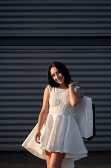 Compras. linda garota elegante vestido branco elegante segurando sacolas de papel no fundo da parede cinza.