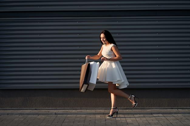 Compras. linda mulher elegante vestido branco elegante, curiosamente olhando para sacolas de compras. parede cinza em fundo.