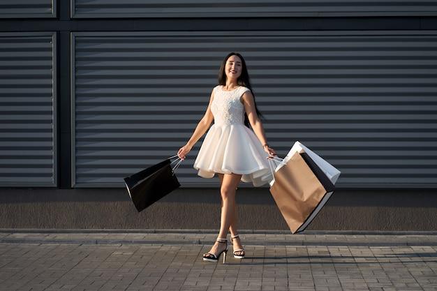 Compras. menina alegre bonita positiva que veste o vestido elegante branco que guarda sacos de compras que andam perto do shopping. filmado em fundo de parede cinza urbano.