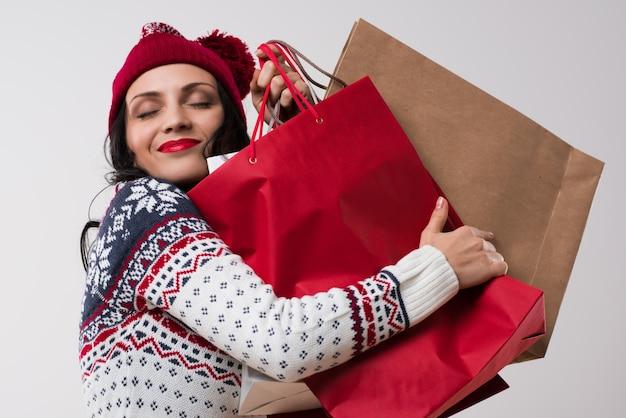 Compras mulher de inverno abraçando sacolas de compras