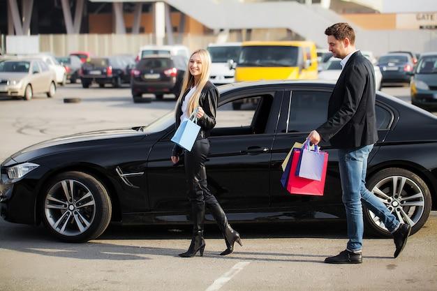 Compras. mulher segurando sacos coloridos perto de seu carro no feriado de sexta-feira negra