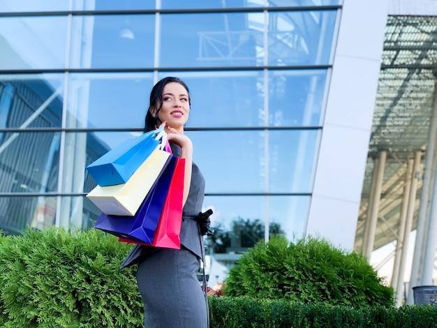 Compras. mulher segurando sacos coloridos perto de seu shopping shooping no feriado de sexta-feira negra