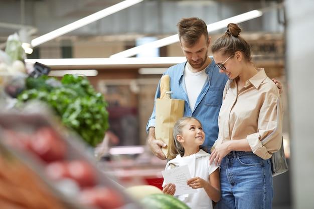 Compras na mercearia jovem e moderna da família