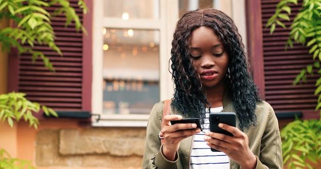 Compras on-line cintura para cima visualização do retrato da mulher multirracial segurando um cartão de crédito e digitando detalhes ...