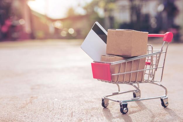 Compras on-line conceito: caixas ou caixas de papel e cartão de crédito no carrinho de compras. conectados