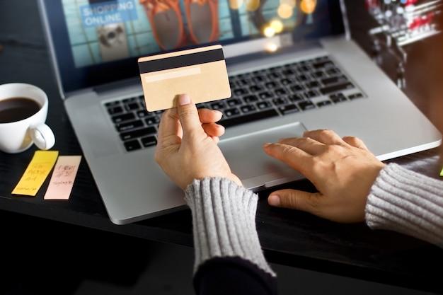Compras on-line conceito. mulher, segurando, ouro, cartão crédito, em, mão, e, shopping online