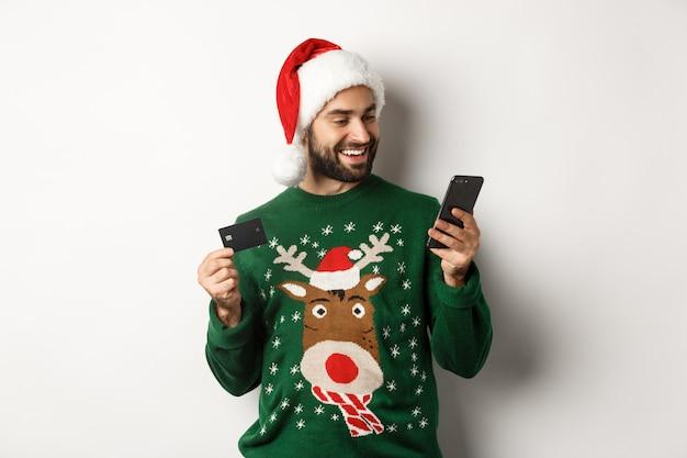 Compras on-line de ano novo e conceito de natal feliz homem barbudo comprando na internet com cartão de crédito ...