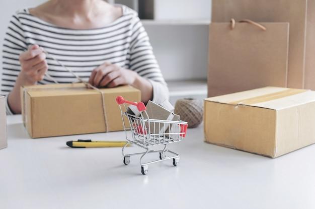 Compras on-line de internet, jovem vendedor mulher preparando pacote para ser enviado mail transportat
