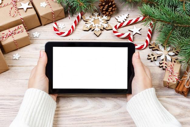 Compras on-line de natal. tela de toque do comprador feminino do tablet, copie o espaço. mulher compra presentes, entre caixas de presente na mesa de madeira branca.