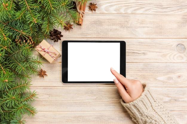 Compras on-line de natal. tela de toque fêmea da mão da tabuleta, vista superior no bakground de madeira, copyspace. fundo de vendas de férias de inverno