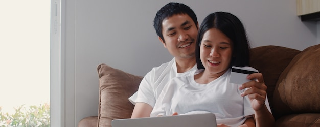 Compras on-line do jovem casal asiático asiáticos em casa. mamãe e papai se sentindo feliz usando a tecnologia laptop e cartão de crédito, comprando produtos para bebês enquanto estava deitado no sofá na sala de estar em casa.