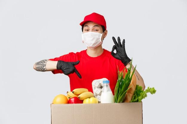 Compras on-line, entrega de alimentos e conceito de pandemia de coronavírus. excelente serviço de correio fornecido pelo entregador asiático, mostra sinal de qualidade garantida, aponta pacote com compras, usa máscara