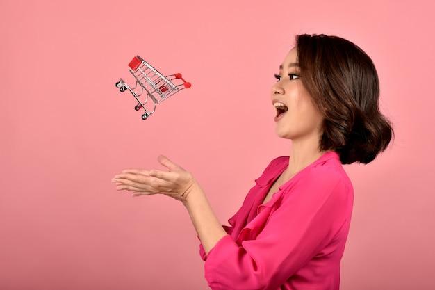 Compras on-line, feliz mulher asiática e mini carrinho de compras engraçado