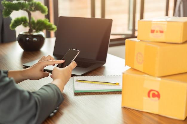 Compras on-line jovens começam pequenos negócios em uma caixa de papelão no trabalho.