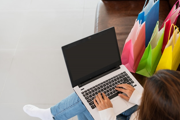 Compras on-line mulher asiática com cartão de crédito e tablet sentado no sofá em casa, estilo de vida digital com tecnologia, conceito de comércio eletrônico