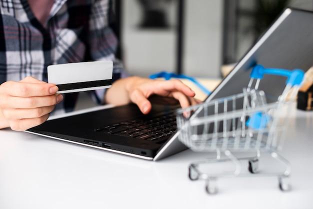 Compras on-line mulher close-up, segurando o cartão de crédito