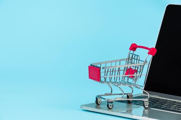 Compras on-line, um carrinho de compras colocado ao lado de um notebook em um azul.
