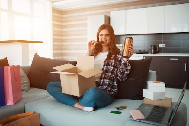 Compras on-line, uma jovem encomendou entrega em domicílio. agora ela se senta no sofá e desembala suas novas compras.