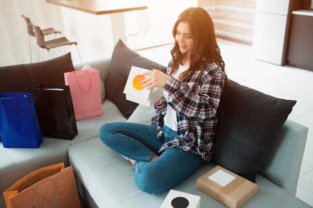 Compras on-line, uma jovem mulher ordenou entrega em domicílio. agora ela se senta no sofá e desembala suas novas compras.