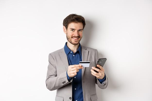 Compras online. bonito empresário em terno pagando com cartão de crédito no smartphone, sorrindo satisfeito para a câmera, em pé no fundo branco.