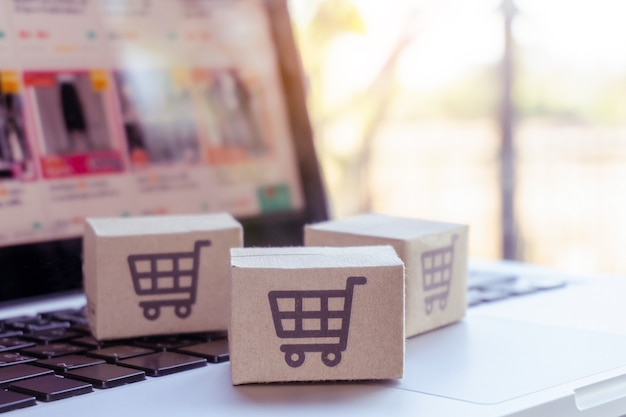 Compras online. caixa de papelão com um logotipo de carrinho de compras no teclado do laptop. serviço de compras na web online. oferece entrega em domicílio