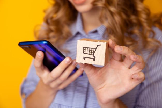 Compras online. caixas de papel na mão e no telefone de uma mulher. conceito de serviço de entrega.