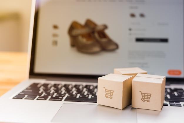 Compras online - caixas de papel ou pacotes com o logotipo de um carrinho de compras em um teclado de laptop que faz compras na tela, serviço de compras na web online e entrega em domicílio.