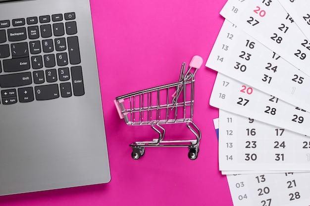 Compras online. carrinho de supermercado com laptop, calendário mensal em uma superfície rosa. vista do topo
