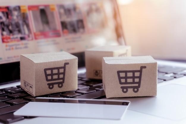 Compras online. cartão de crédito e caixa de papelão com um logotipo de carrinho de compras no teclado do laptop. serviço de compras na web online. oferece entrega em domicílio