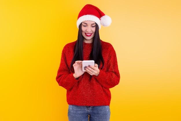 Compras online de natal. a compradora faz o pedido na tela do smartphone com espaço de cópia. mulher compra presentes para a véspera de natal. promoções de férias de inverno