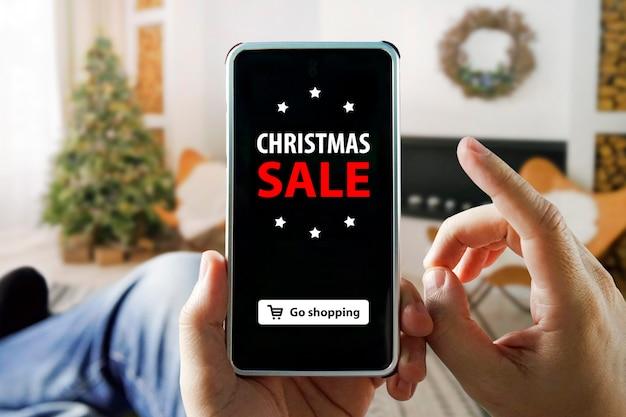 Compras online de natal com telefone. homem senta em um apartamento e faz compras por meio de um smartphone em uma loja online. árvore de natal, presentes, luzes e decorações em segundo plano.